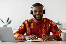 E-learning. Happy Black Man Wearing Headset Study Online With Laptop At Home