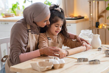 Cute Little Girl And Muslim Mom Rolling Up Dough Together In Kitchen
