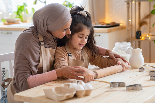 Photo Cute little girl and muslim mom rolling up dough together in kitchen