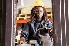 Focused Young Black Female Logistic Worker In Protective Uniform Operating Fork Lift In Warehouse, Pulling Lever. Low Angle. Female Labor Concept