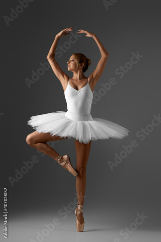 Fotografie, Obraz graceful ballerina in white tutu and pointe shoes on gray background
