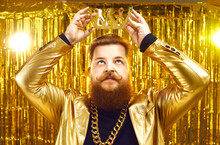 Funny Rich Young Man Wearing Gold Chain And Shiny Glittering Golden Jacket Putting On King's Crown With Serious Face Expression. Ambitious Personality, Arrogance, Megalomania, Greed For Power Concept