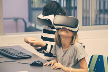 Portrait Of Little Kids Using VR Headsets And Having Fun. Happy Cute Multiethnic Girls Sitting At Desk During Computer Lesson And Playing In Virtual Reality. Informatics And Education Concept