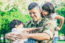 Happy Disabled Military Dad Walking With Two Children In Park. Girl Holding Wheelchair Handles, Boy Resting On Dads Lap. Veteran Of War Or Disability Concept