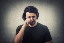 Portrait Of Desperate Young Man Crying And Wiping The Tears With His Hand Isolated On Grey Wall Background. Dissatisfied And Disappointed Guy Sobbing And Weeping To Camera.