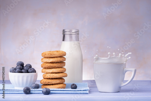 on lavender blue table, breakfast food with wholemeal shortbread cookies, blueberries and fresh milk with splash