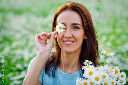 Obraz na plátně A young woman in a blue dress on a chamomile field