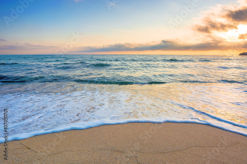 Obraz summer vacation at the seaside. beautiful seascape at sunrise. calm waves wash the golden sandy beach. fluffy clouds on the sky - fototapety do salonu