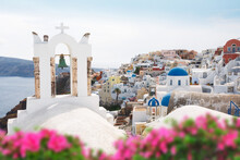 Oia Village  Through Flowers And  Traditional Greek White Church Arch With Cross And Bells In Oia Village Of Cyclades Island, Santorini