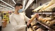 Man wearing disposable medical mask choosing bread during shopping at bakery supermarket store. Protection and prevent measures while epidemic time.