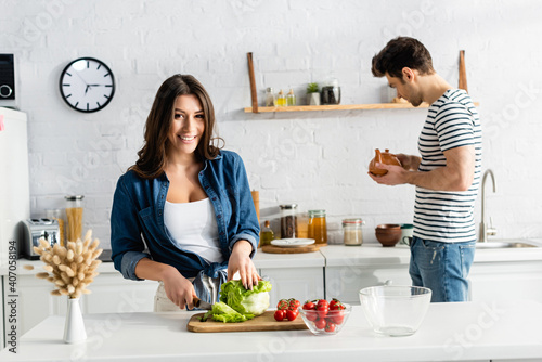 Tela happy woman cutting lettuce near ingredients on kitchen table and boyfriend with