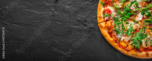 Fototapeta Pizza with chicken, bacon, cheese, tomato and arugula. Italian pizza on Dark grey black slate background obraz