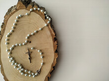 Catholic Rosary Prayer On A Wooden Saw Cut Birch.