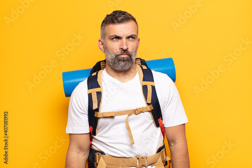 Fototapeta adult man feeling sad, upset or angry and looking to the side with a negative at