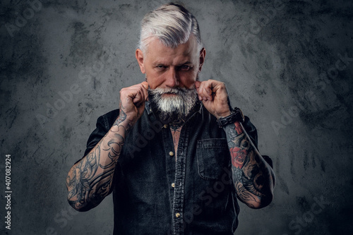 Obraz na plátne Portrait of old and confident man with tattooed body and gray hairs which poses in dark background
