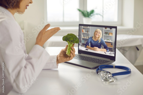 Obraz Online wellness consultation via video call: Doctor, dietitian or nutritionist sitting at laptop, holding broccoli, talking to senior patient and giving her tips on happy long life and healthy diet - fototapety do salonu