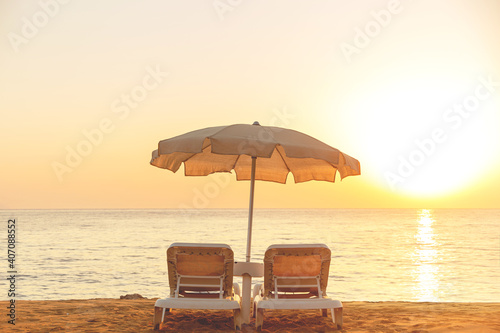 Fotografia Beige cotton beach umbrella with two sunbeds by the sea
