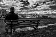 Young Man Sitting On A Bench Looking Out At Sea In The Town Of Chania In The Greek Island Of  Crete. Framing Art, Black & White