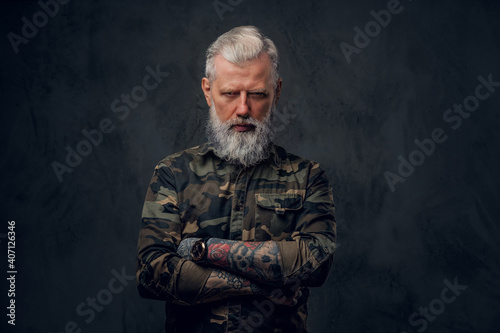 Fototapeta Brutal martial grandfather dressed in military clothing poses in dark background with crossed arms