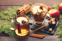 Tasty Drink With Spices And Apple Slices In Cups On Wooden Background