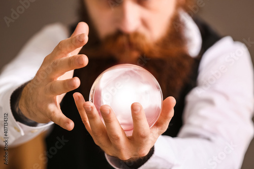 Fotografering Male fortune teller with crystal ball reading future, closeup