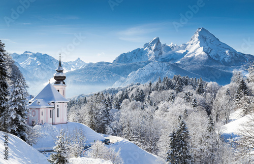 Alpine Church after morning snowfall in mountain. Church covered with snow in the Alps. In the background the peaks of the mountains. Famous Watzmann massif in the background, Bavaria, Germany