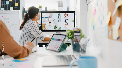 Obraz Asia businesspeople using desktop talk to colleagues discussing business brainstorm about plan in video call meeting in new normal office. Lifestyle social distancing and work after corona virus. - fototapety do salonu