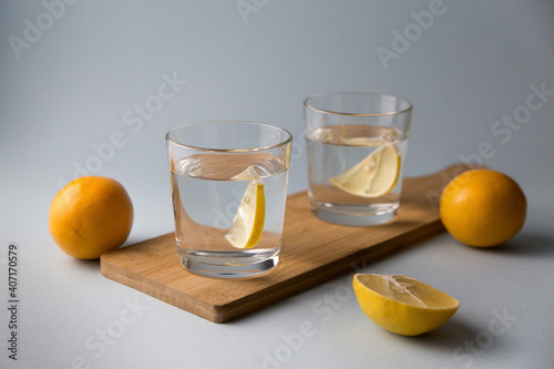 Fotografía Water with lemon in two glasses on a wooden stand on a light blue background, sl