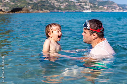 Photo Little child is crying affraid of water in the sea