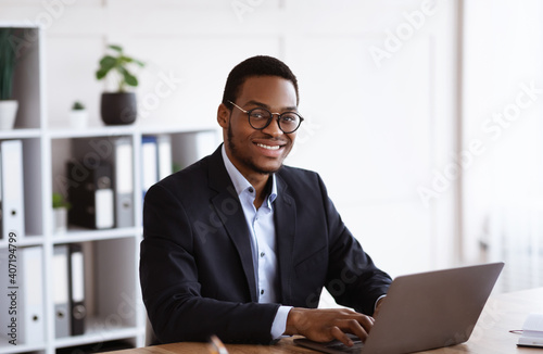 Obraz na plátně Cheerful african businessman working with laptop in office