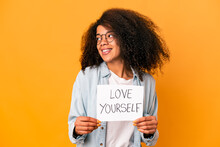 Young African American Curly Woman Holding A Love Yourself Placard Looks Aside Smiling, Cheerful And Pleasant.