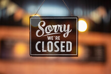 Sorry We're Closed Sign. Grunge Image Hanging On A Glass Door.