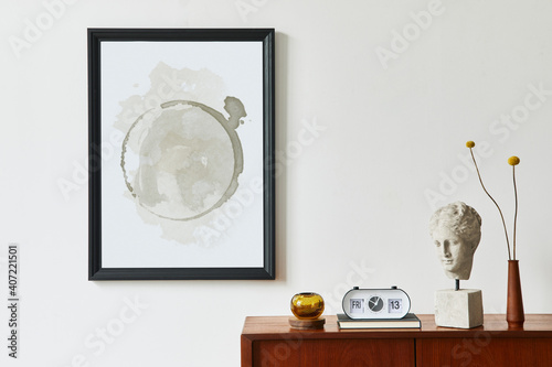 Retro modern compositon of living room interior with design teak commode, black mock up poster frame, clock, dried flower, decoration, white wall and personal accessories. Template.