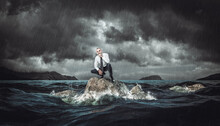 Thoughtful Man On A Rock In The Rough Sea During A Storm.