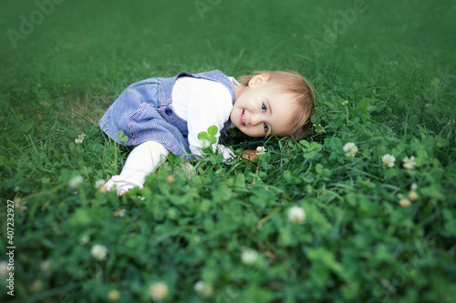 Fotografija A child lies smiling in a clover field. Lovely little girl.