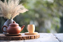 Bamboo Wooden Tea Cup And Brown Clay Kettle With Dry Flower Pot On Table