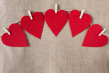 Five Red Hearts On Wooden Pegs Hang On A Rope On A Background In The Form Of Burlap. Valentine's Day Theme. Free Space For Text.