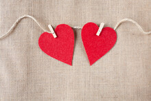 Two Red Hearts On Wooden Pegs Hang On A Rope On A Background In The Form Of Burlap. Valentine's Day Theme.  Free Space For Text.