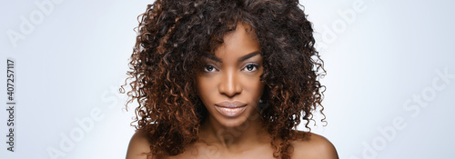 Beautiful black woman . Beauty portrait of african american woman with clean healthy skin on beige background. Smiling beautiful afro girl.Curly black hair - fototapety na wymiar