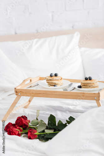 Obraz wooden tray with delicious pancakes and blueberry near red roses on white bedding, valentines day concept - fototapety do salonu