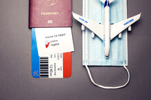Traveling During COVID-19 Virus, Passport With Airline Ticket, Covid-19 Negative Test, Medical Mask And Plane On Grey Background, Airport Security Health And Safety Check Concept