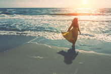 Seascape On A Sunny Day. Girl On The Beach. A Young Girl In A Yellow Fluttering Dress Walks Along The Seashore. The Girl Looks At The Sea