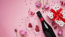 Concept For Banner,greeting Card For Valentine's Day.Bottle Of Champagne Wine,glasses With Glittering Confetti In Shape Of Heart,roses,serpentine And Gift Box On Pink Background, Flat Lay,copy Space.