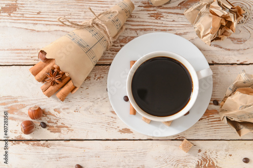 Tasty coffee with cinnamon in cup on wooden background
