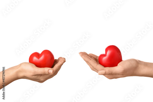 Fotografía Hands with red hearts on white background
