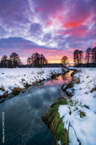 Piękny zimowy zachód słońca nad brzegiem rzeki