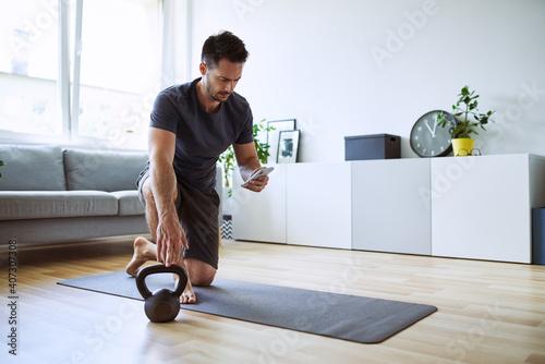 Fototapeta Man setting up online workout app at home obraz