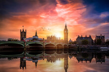 The Westminster Palace And The Big Ben Clocktower By The Thames River In London, United Kingdom, During A Colorful Sunset