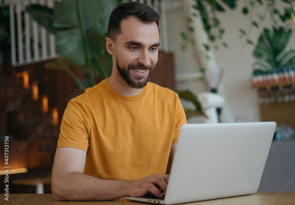 Fototapeta Attractive smiling man using laptop computer, working from home. Portrait of young freelancer copywriter typing, sitting at workplace. Student studying, distance learning, searching, online education