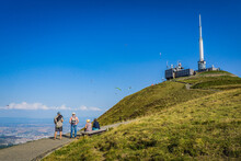 People Looking At Paragliders Launching Their Flight From The Top Of The Puy De Dome Volcano In Auvergne, France